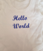 White sleeveless new  baby vest ( Hello world )